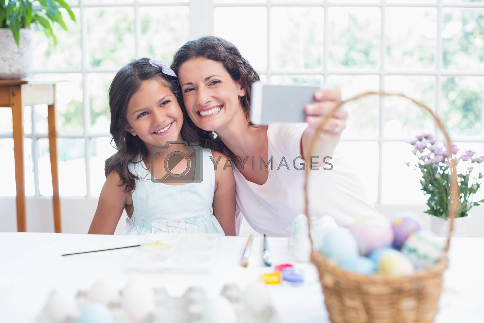 Happy mother and daughter taking selfie in the living room