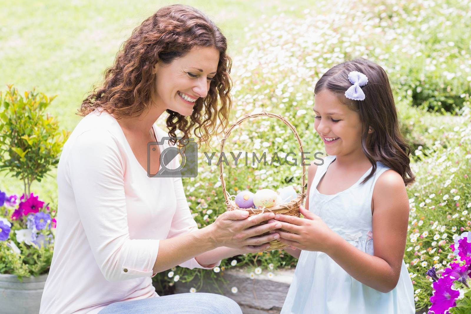 Royalty free image of Happy mother and daughter collecting easter eggs by Wavebreakmedia