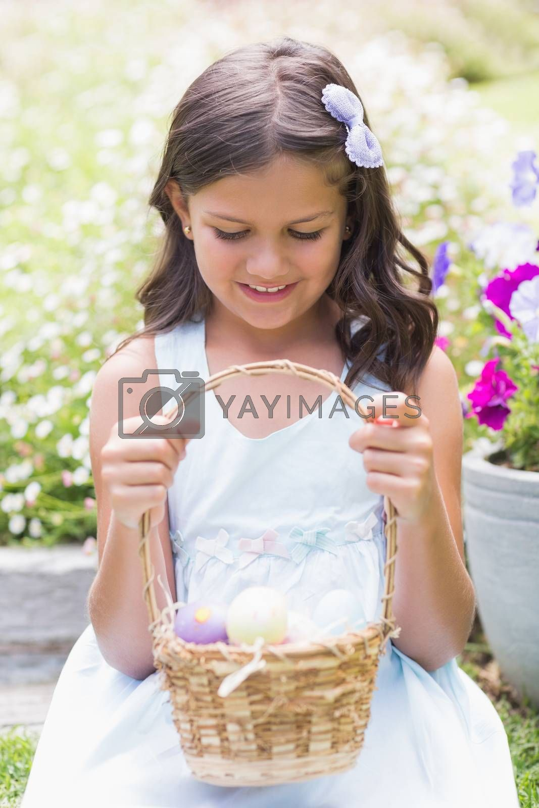 Royalty free image of Happy girl collecting easter eggs by Wavebreakmedia