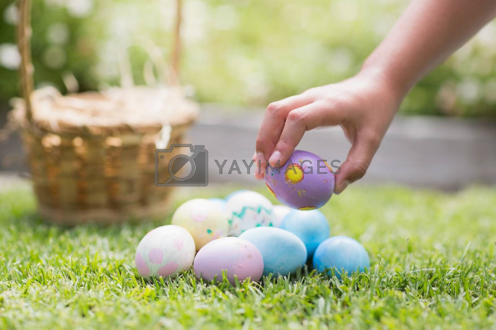 Little girl collecting easter eggs  by Wavebreakmedia
