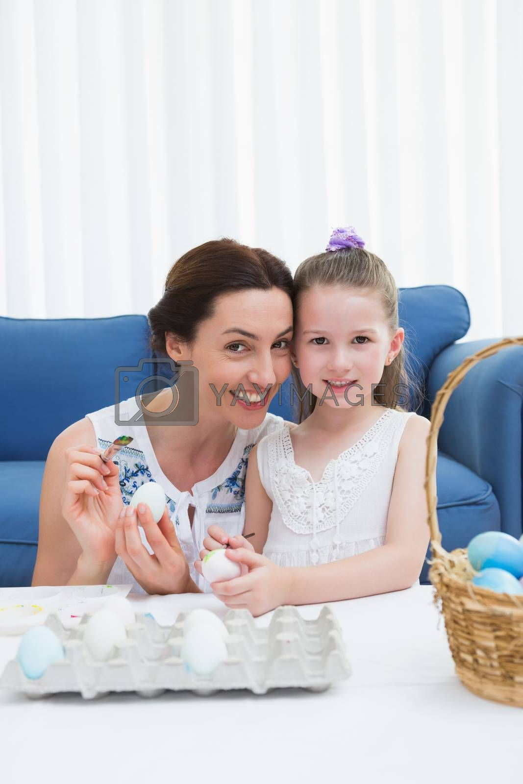 Mother and daughter painting easter eggs at home in the living room