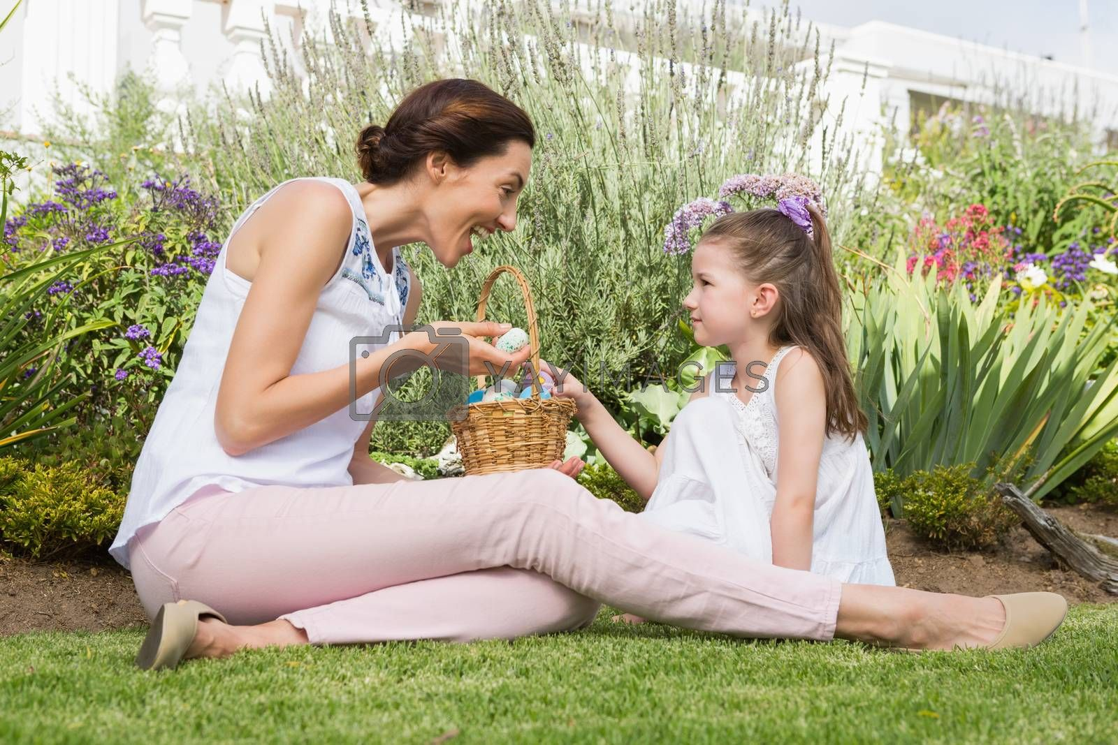 Mother and daughter collecting easter eggs outside in the garden