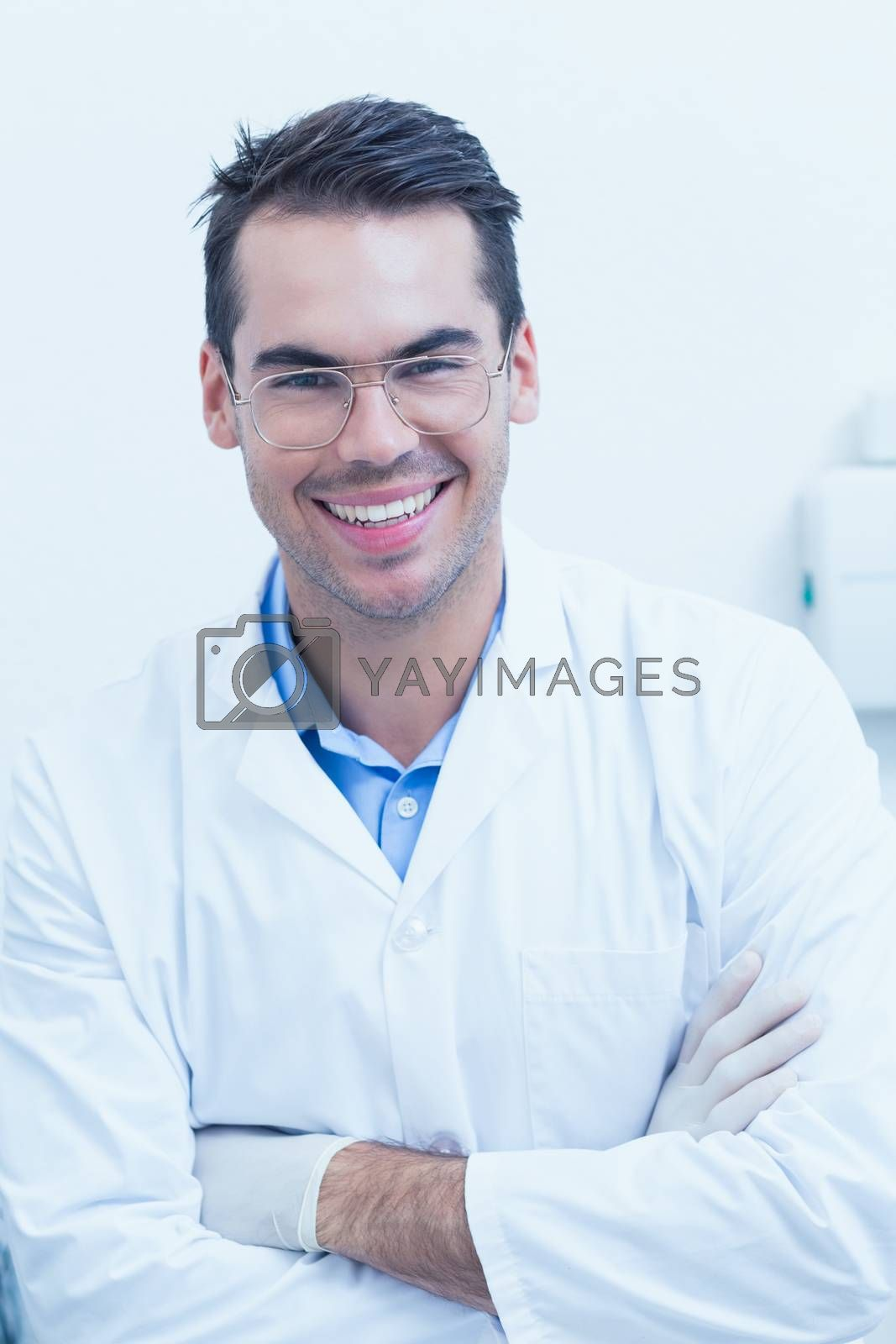 Portrait of happy male dentist with arms crossed