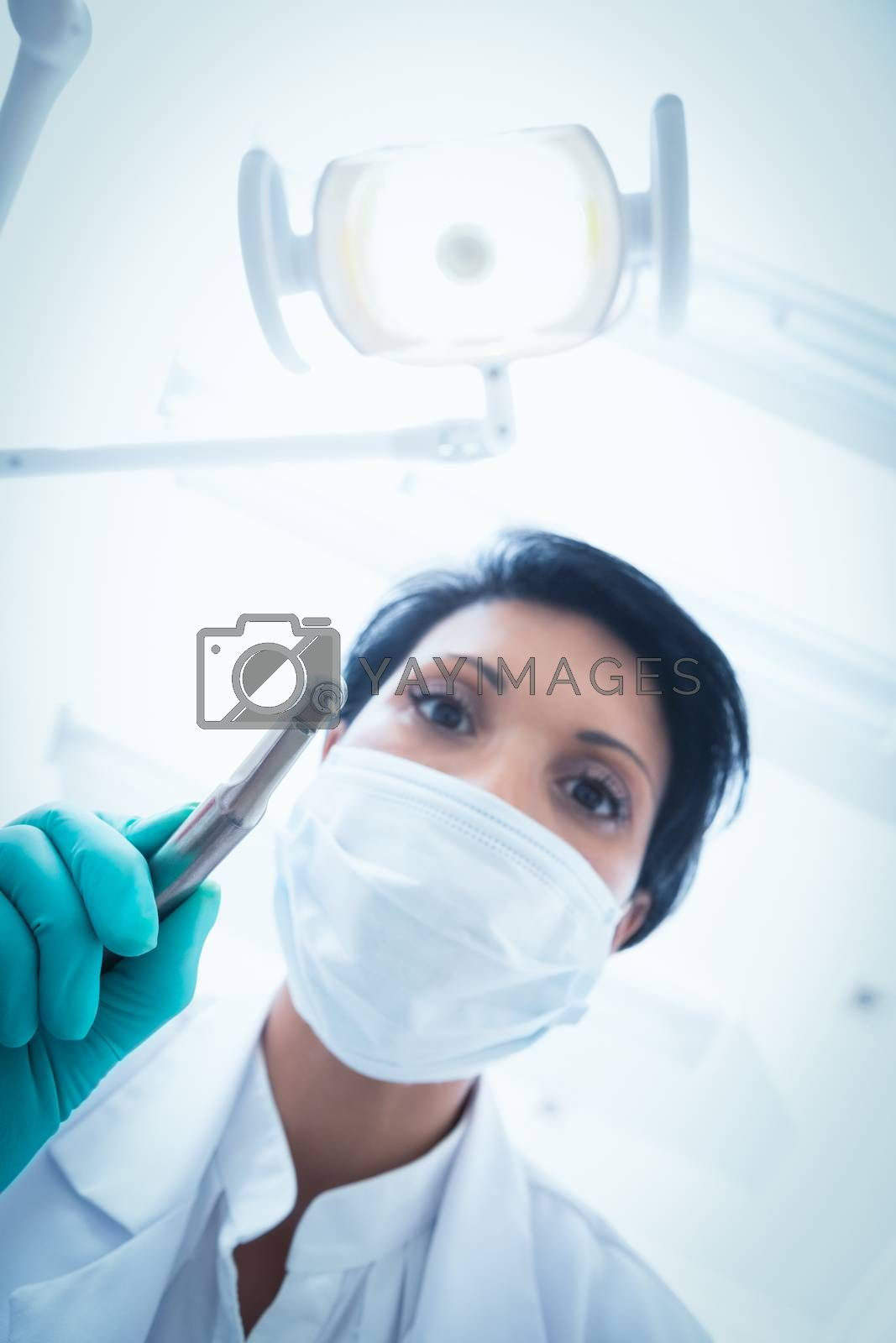 Low angle view of female dentist in surgical mask holding dental drill