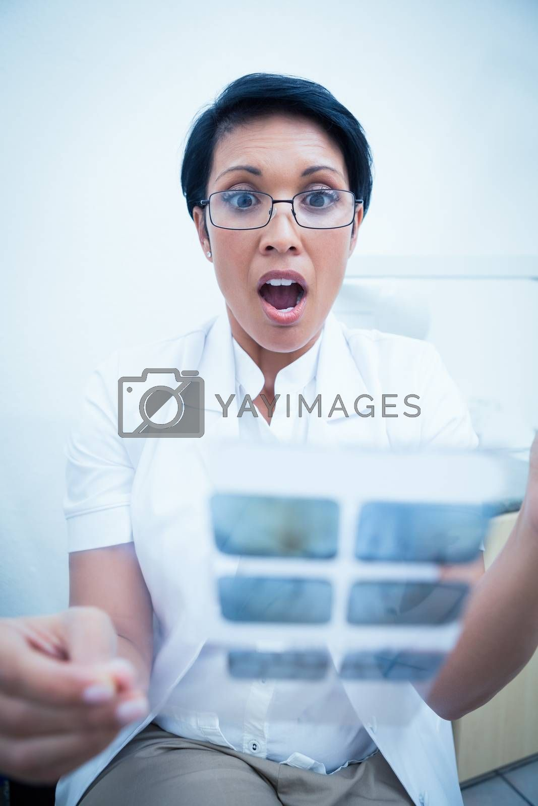Shocked female dentist looking at x-ray