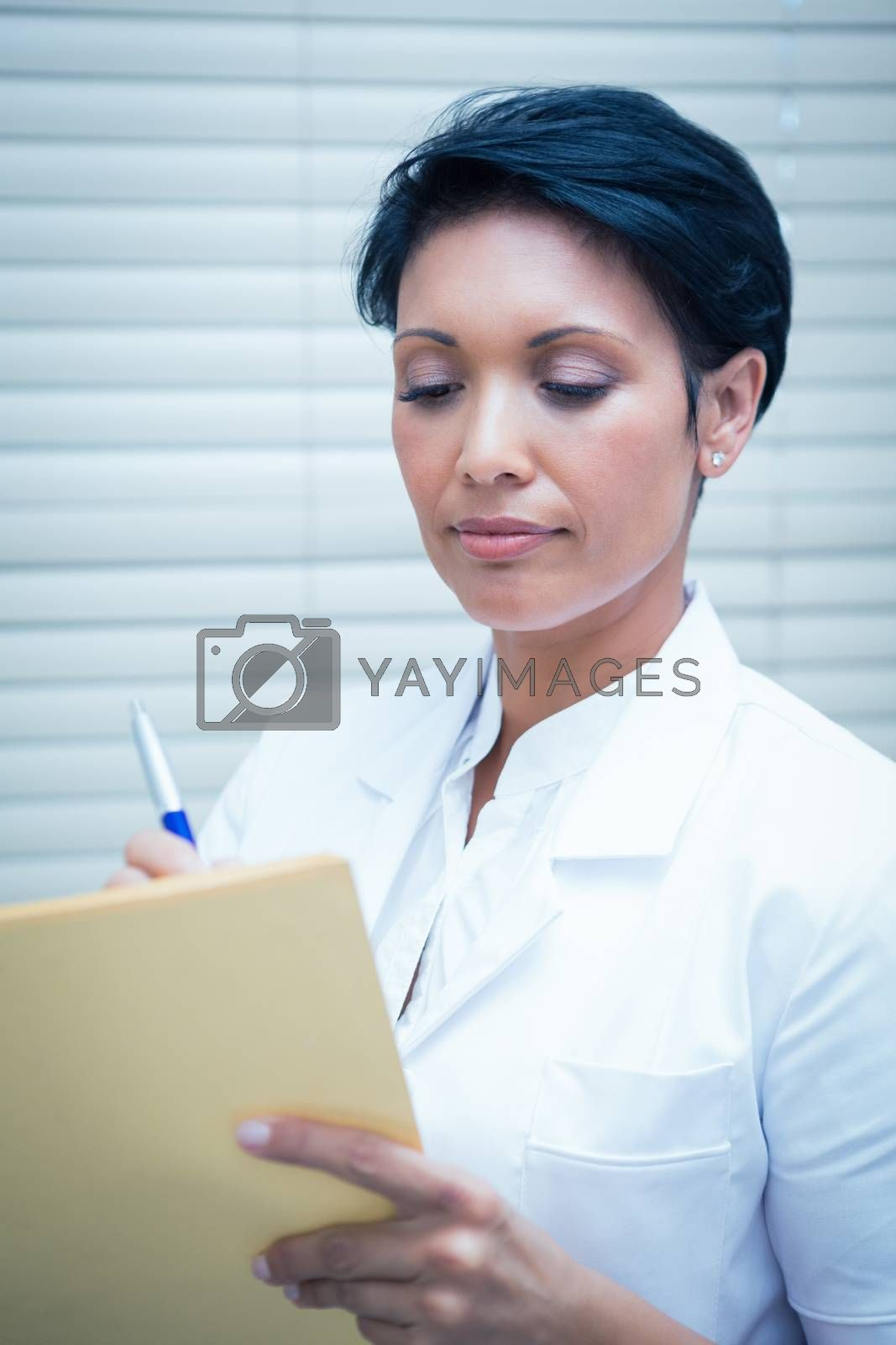 Serious female dentist reading reports