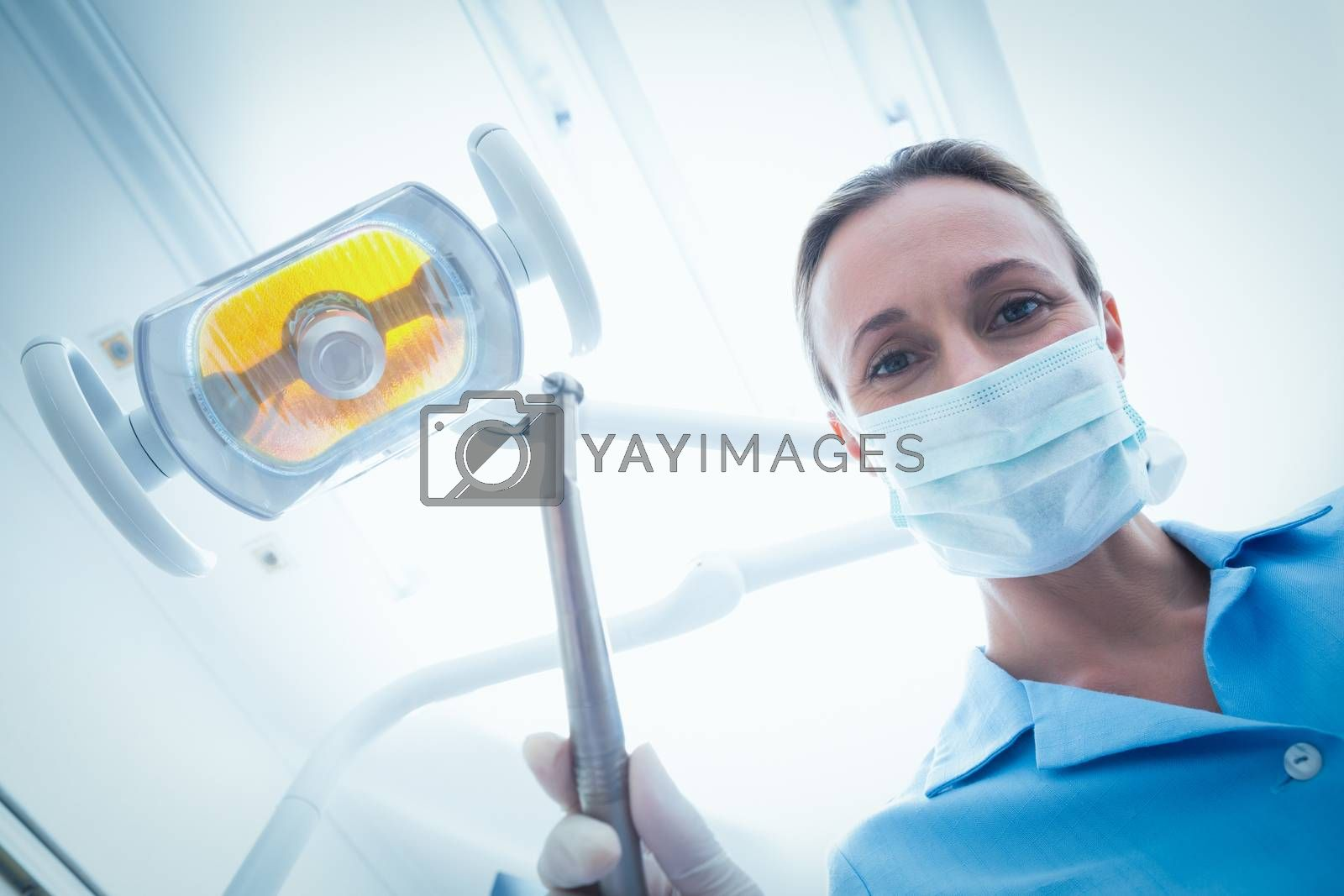 Low angle portrait of female dentist in surgical mask holding dental tool