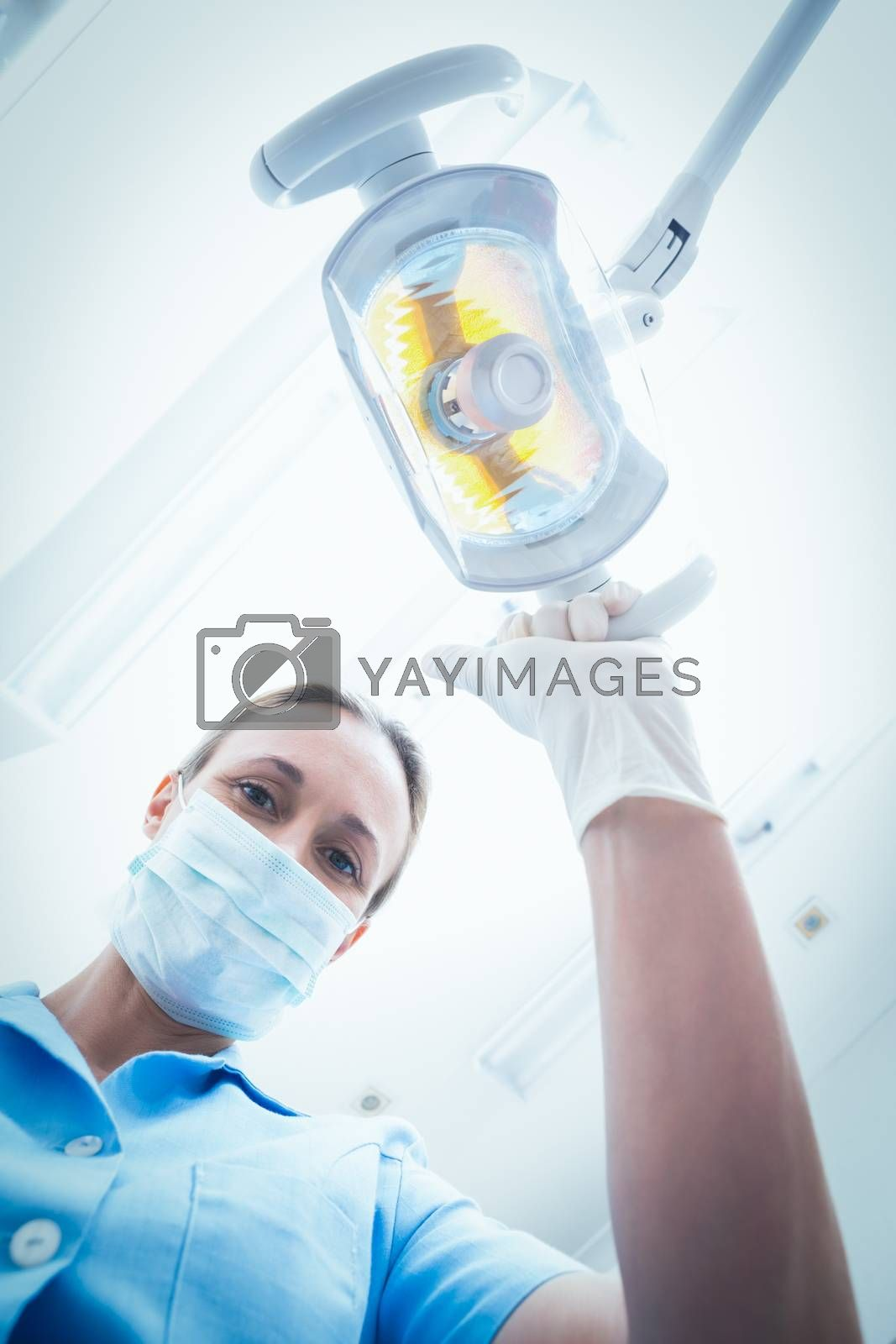 Low angle portrait of female dentist adjusting light