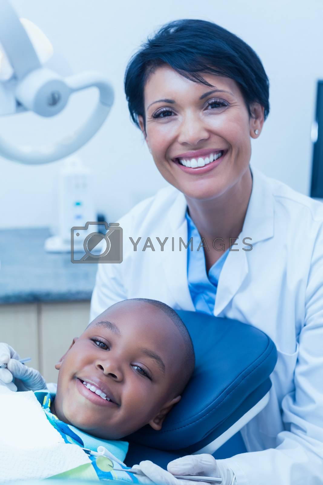 Portrait of female dentist examining a boys teeth in the dentists chair