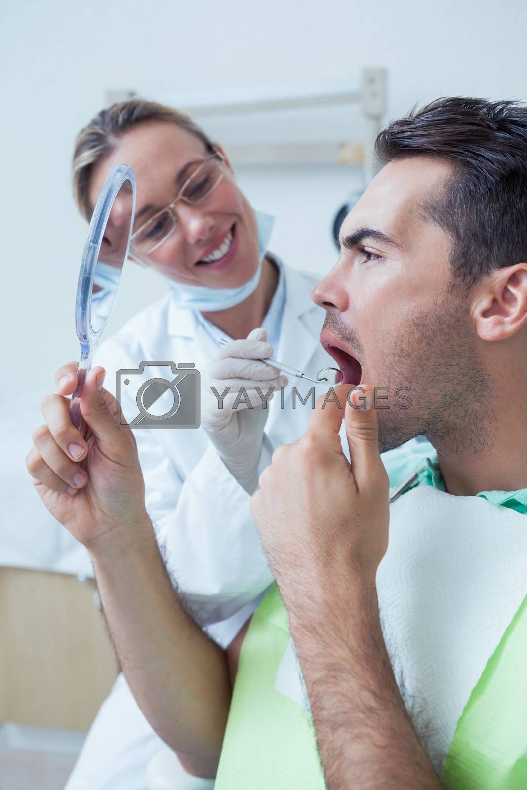 Side view of young man looking at mirror by female dentist
