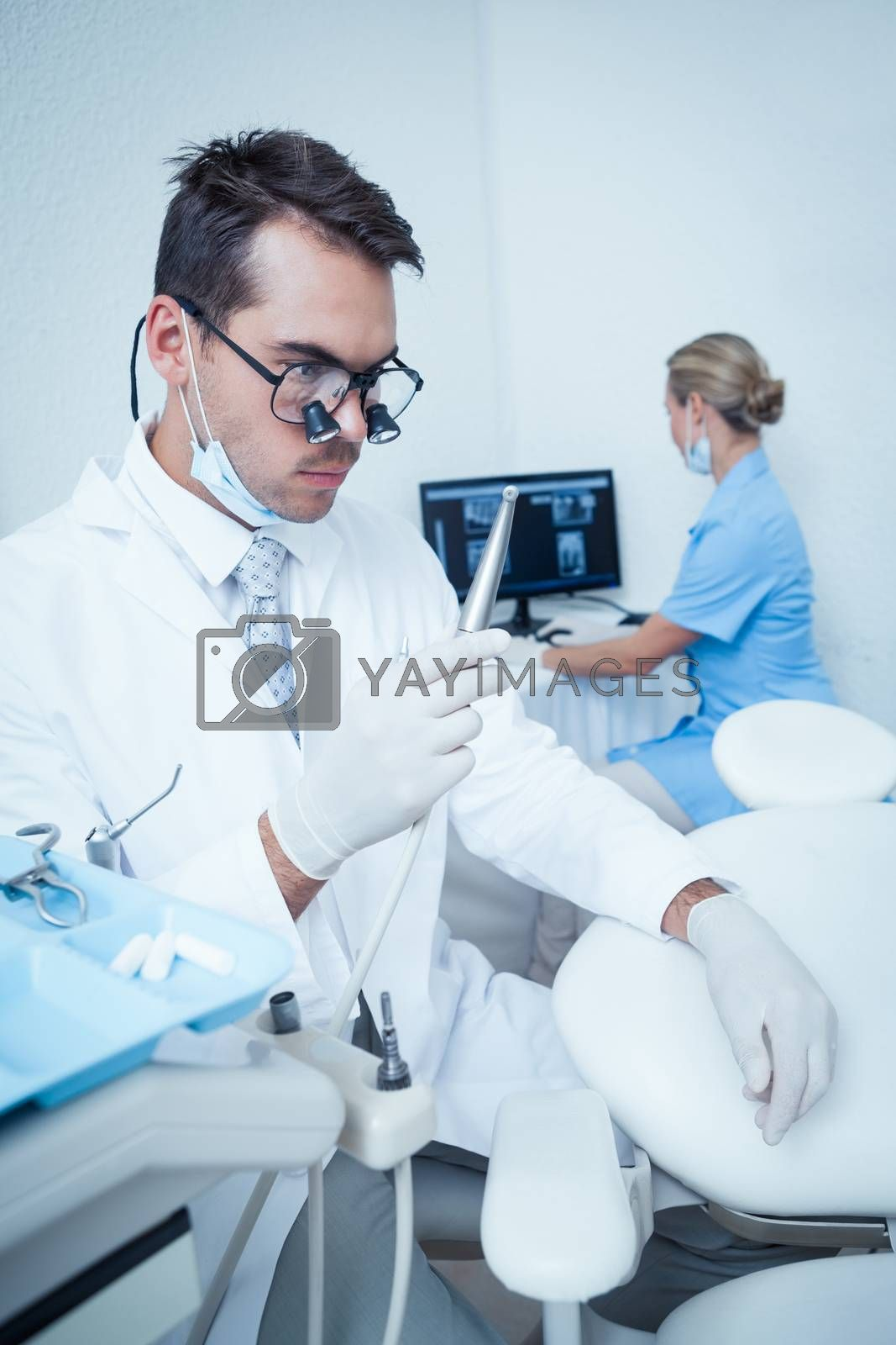 Dentist looking at dental drill by Wavebreakmedia