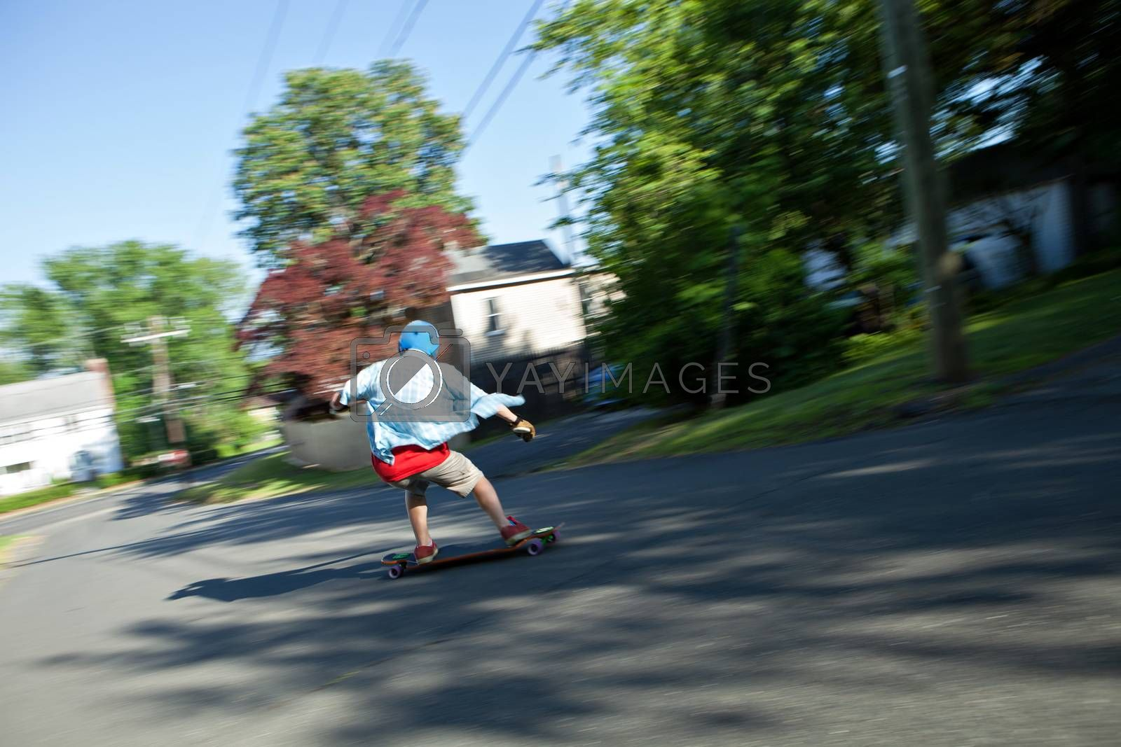 Longboarder skating on an urban road. Slight motion blur from panning technique to capture movement.