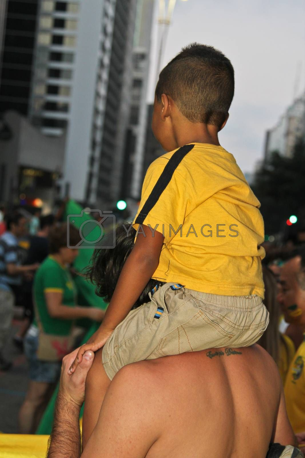 SAO PAULO, BRAZIL - APRIL 12, 2015: One unidentified boy and a man in the middle of crowd at protest against federal government corruption on Sao Paulo Brazil. Protesters call for the impeachment of President Dilma Rousseff.