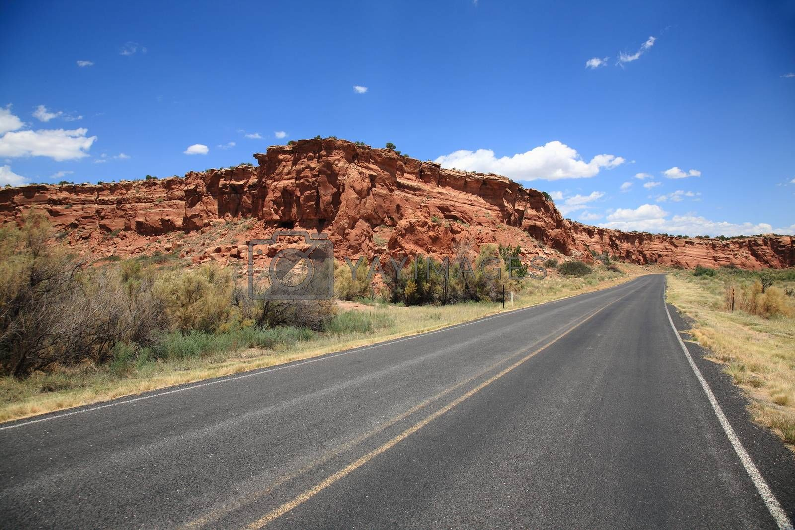 Road heads towards the mountains and buttes in Southwestern United States