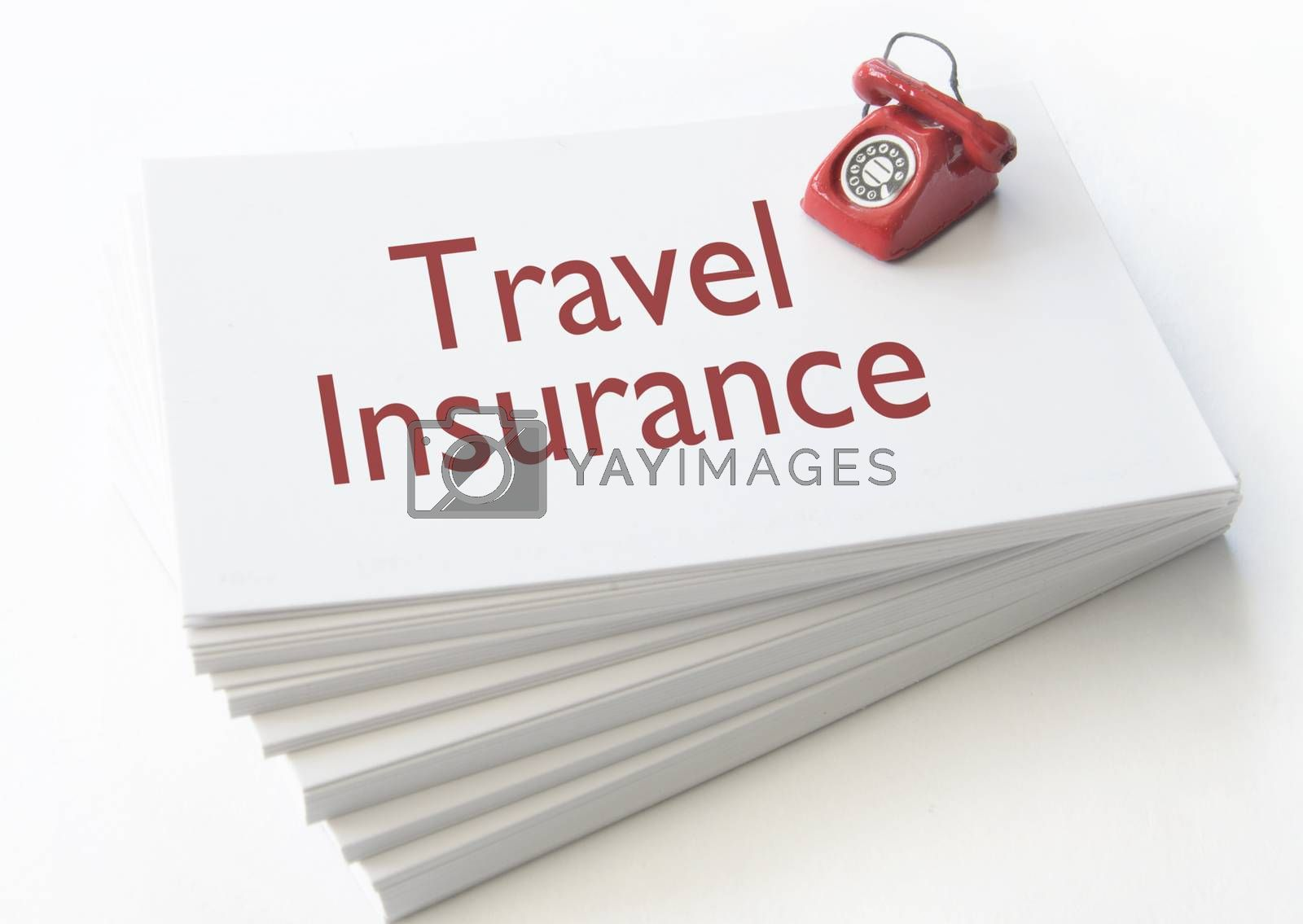 Small telephone on top of a stack of contact cards with travel insurance