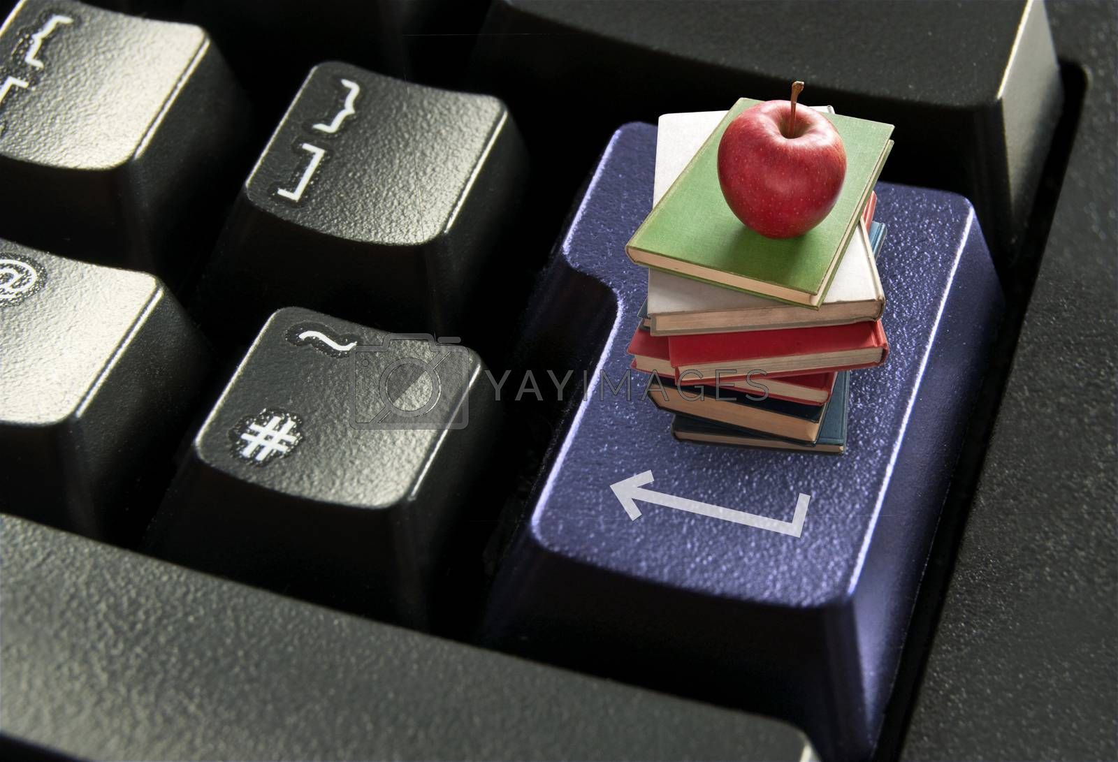 Stack of books with red apple on top of a computer enter key