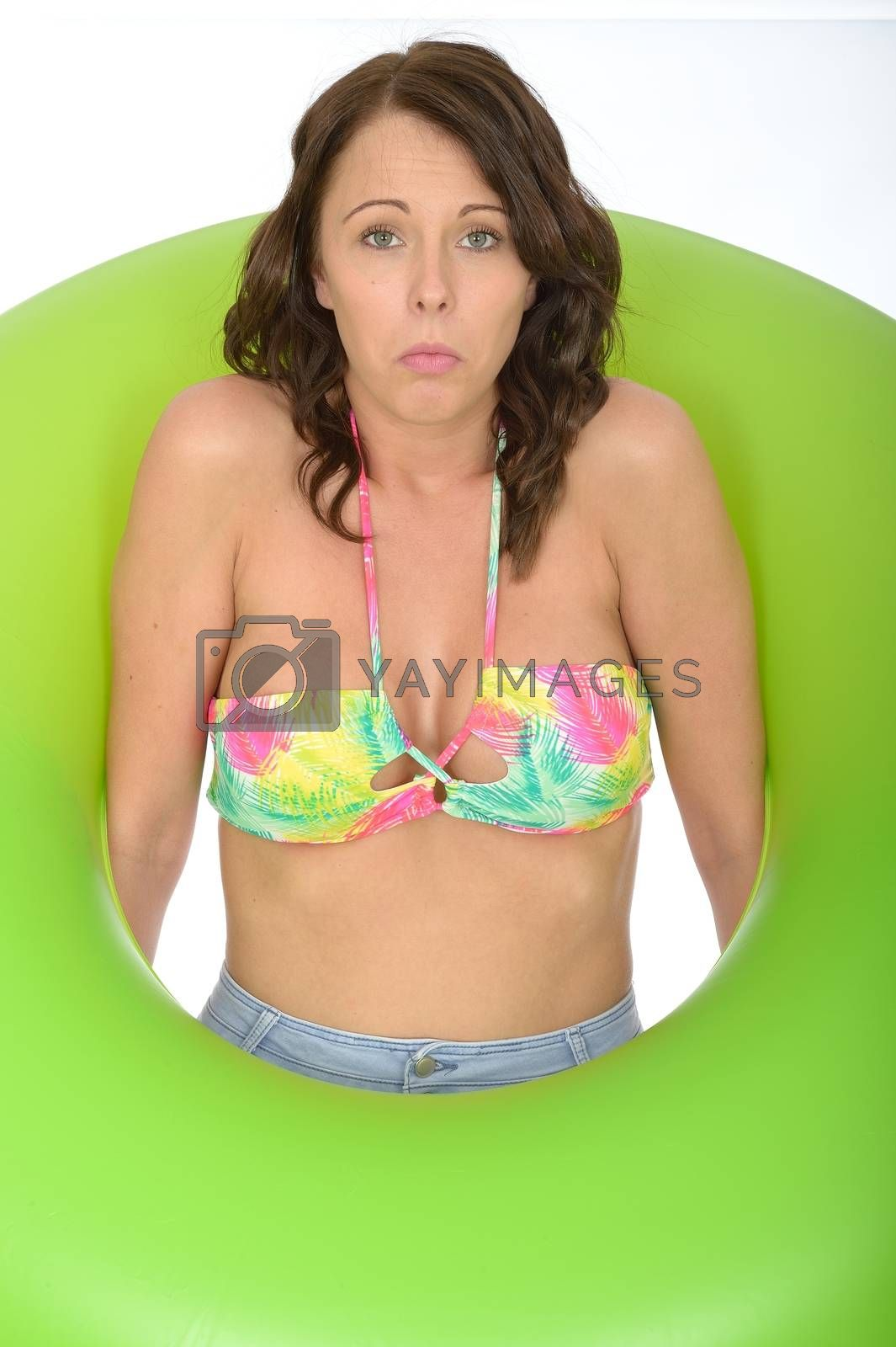 Attractive Unhappy Young Woman Looking Through a Green Rubber Ring
