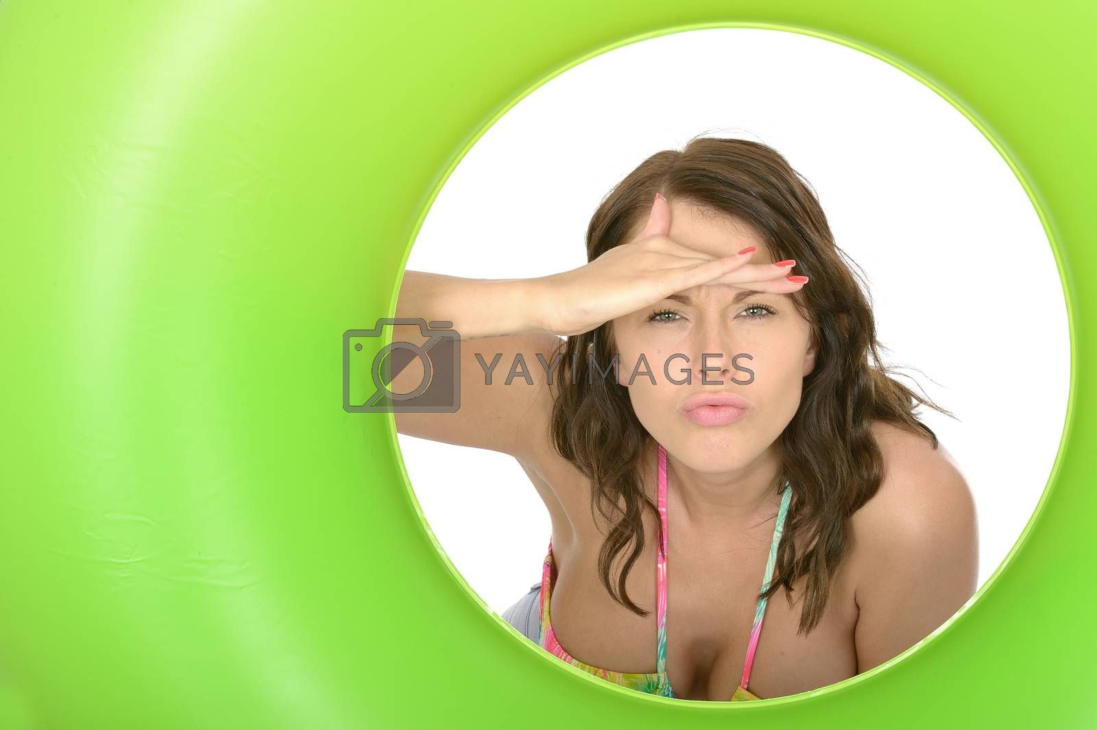 Attractive Young Woman Peering as if Spying Through a Green Rubber Ring