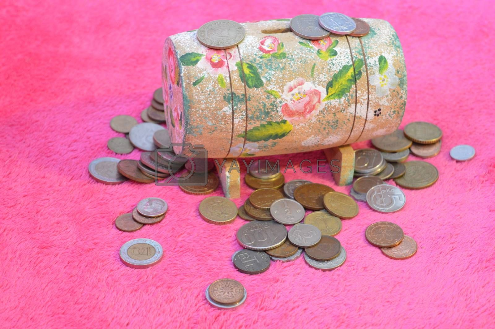 Golden coins and wooden money box, on pink background