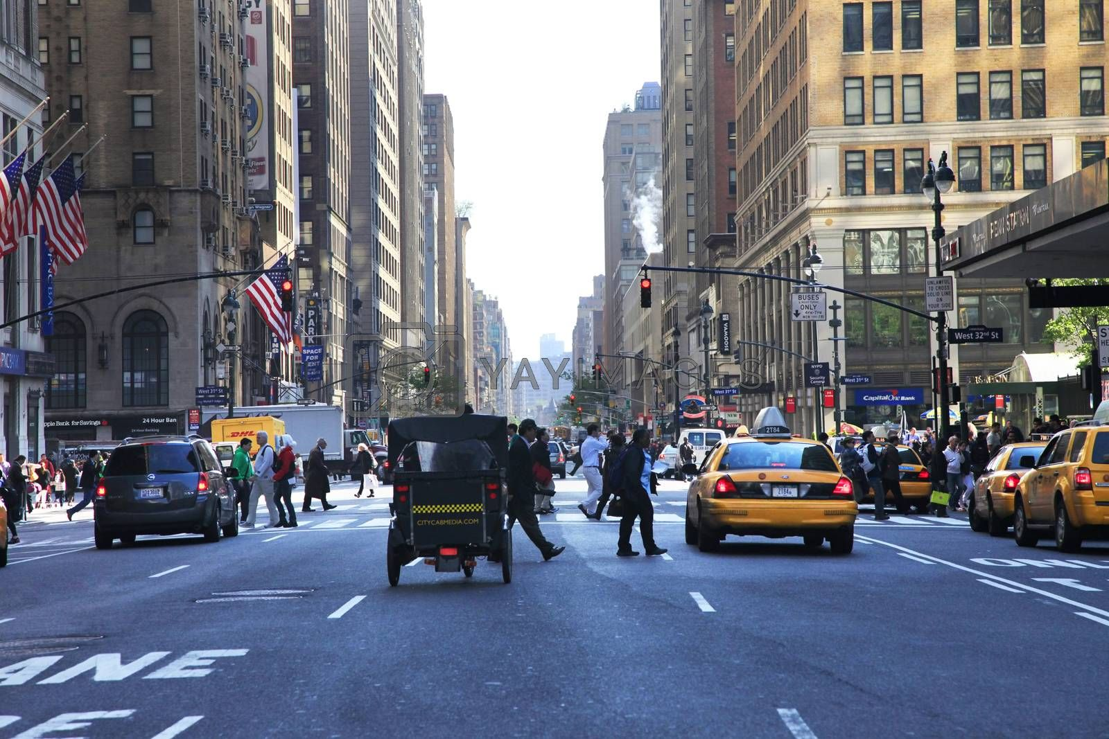 New York, NY, USA - May 15, 2013 : Busy traffic on the street. Intersection along 7th Ave & West 32nd St in midtown Manhattan in New York
