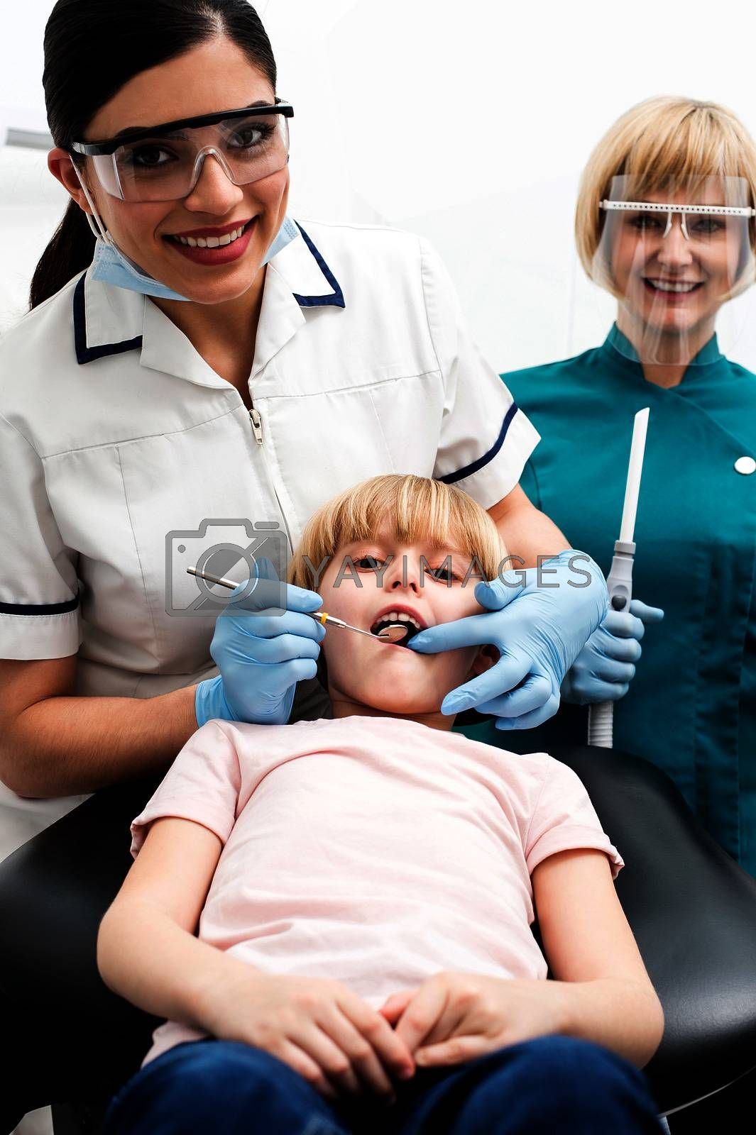 Dentist and assistant examining a little girl patient