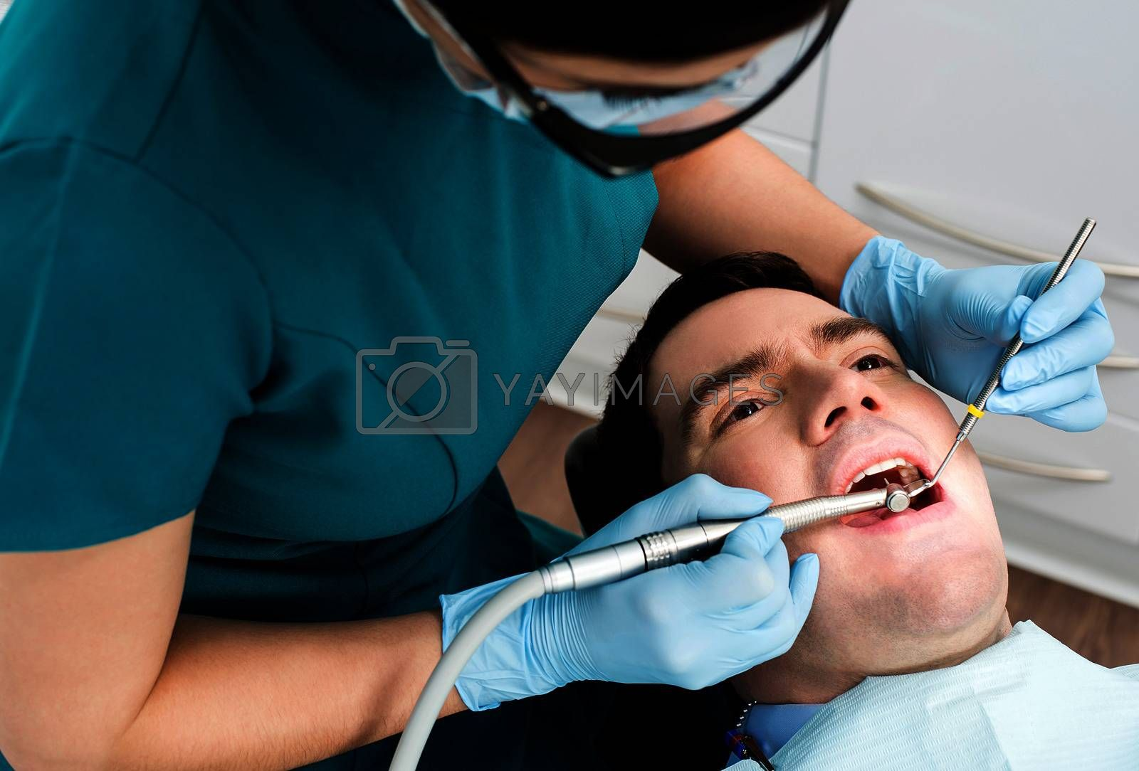 Male with open mouth during oral checkup at dentist