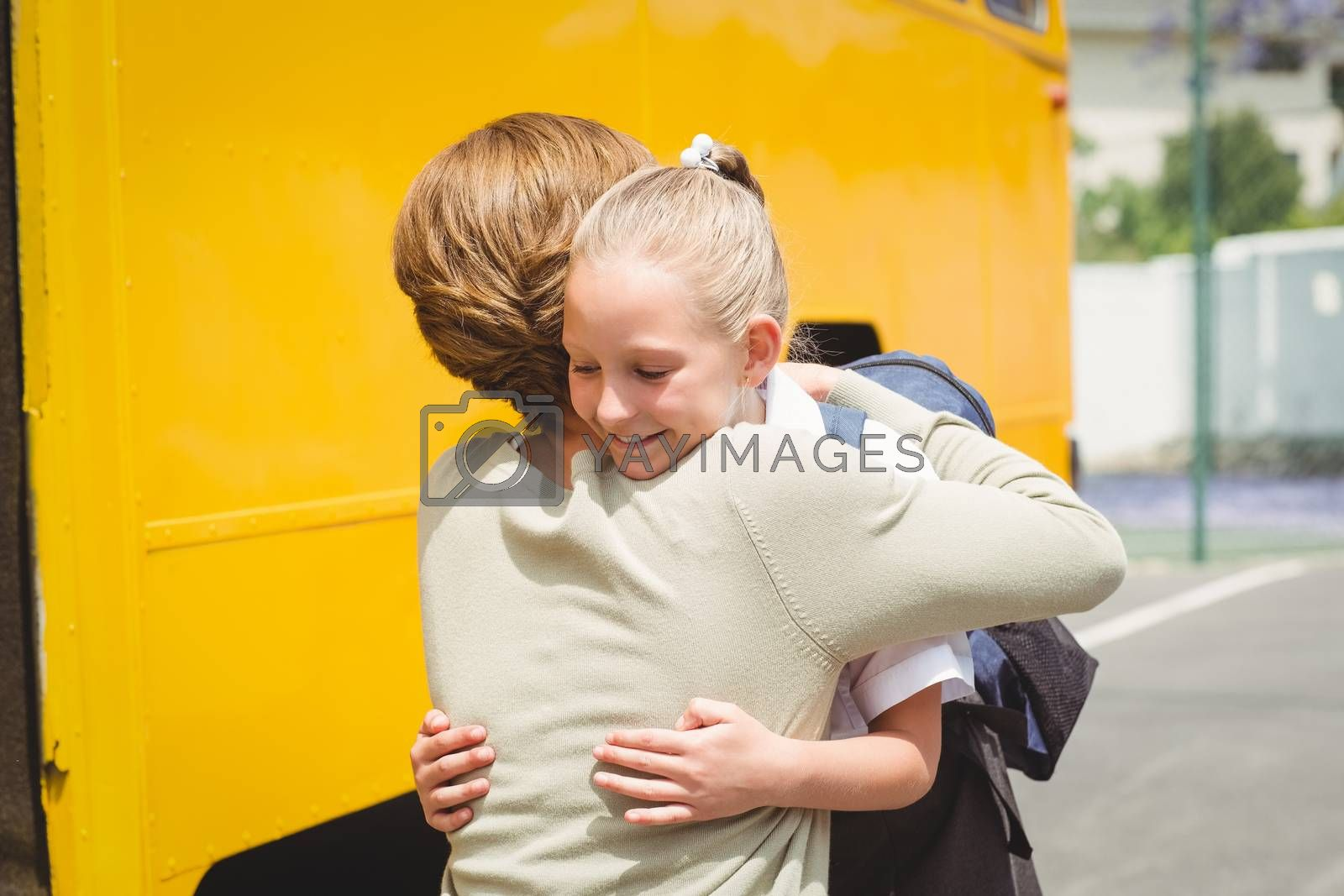 Mother hugging her daughter by school bus by Wavebreakmedia