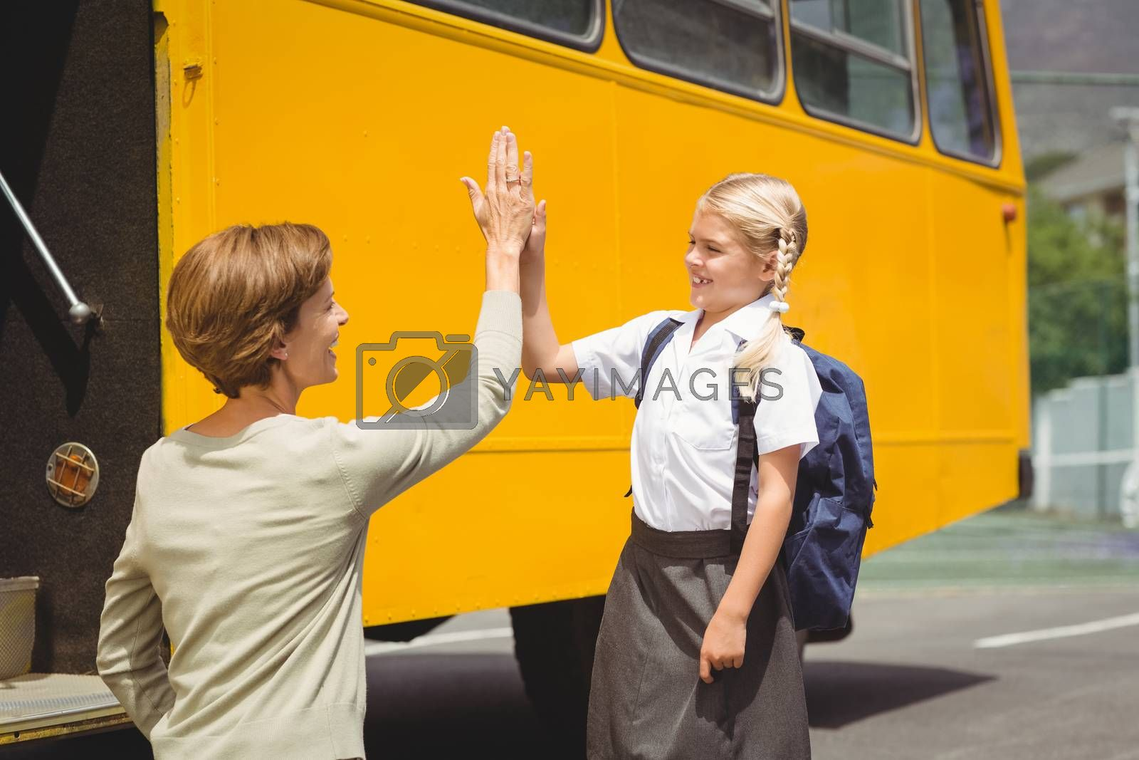Mother with her daughter by school bus outside the elementary school