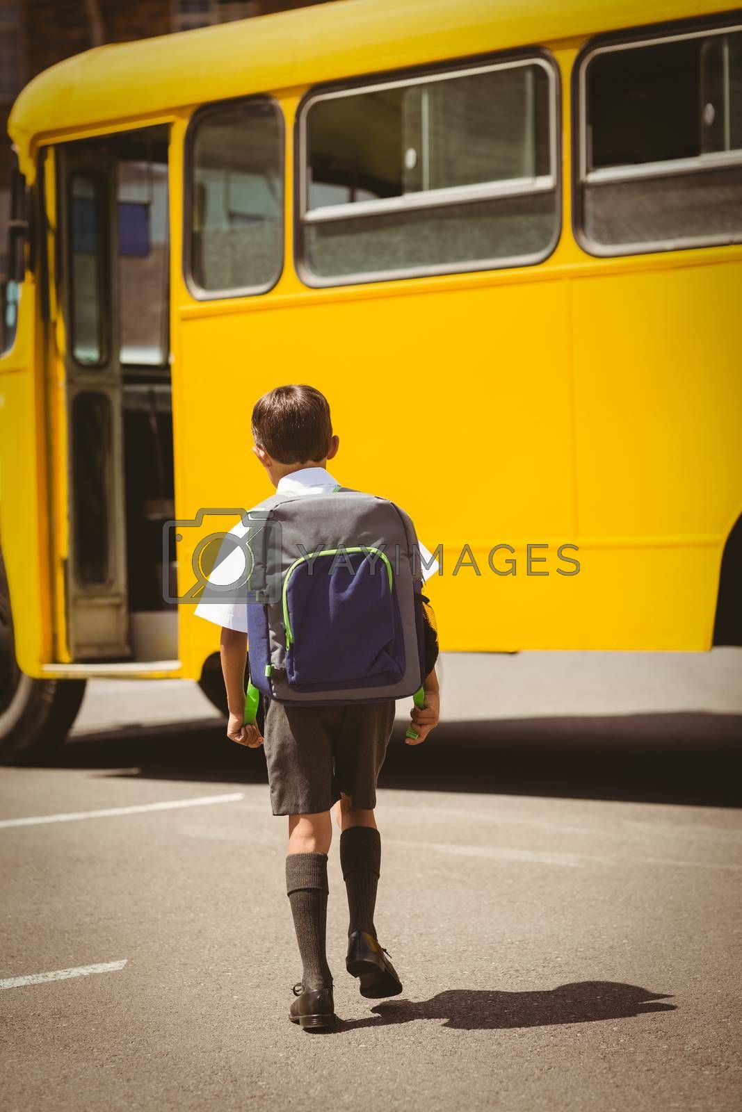 Cute pupil walking to the school bus outside the elementary school