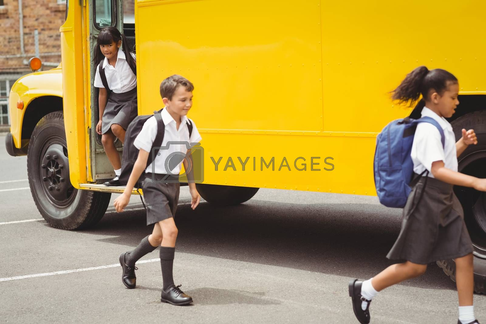 Cute schoolchildren getting off the school bus outside the elementary school