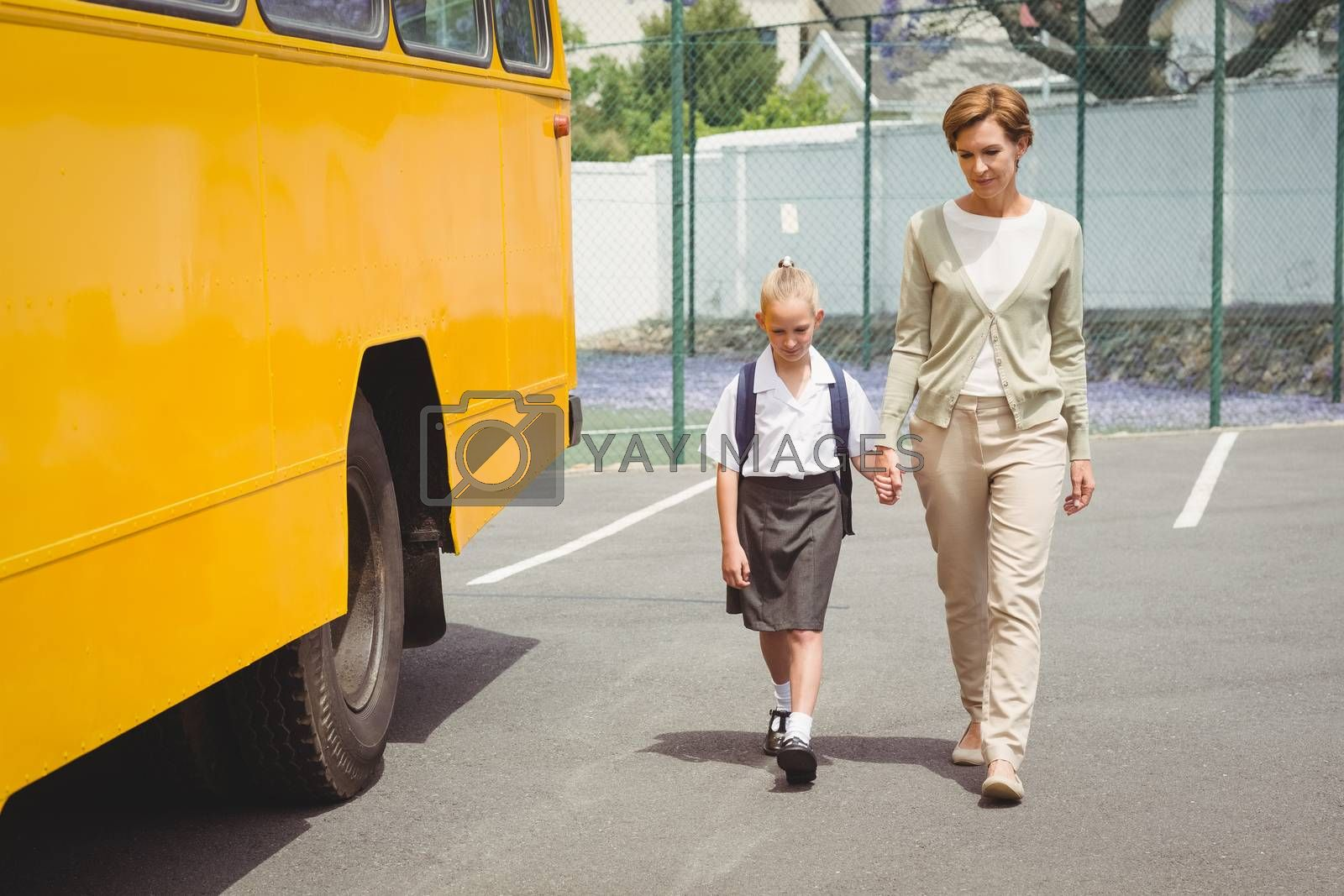 Mother walking her daughter to school bus outside the elementary school