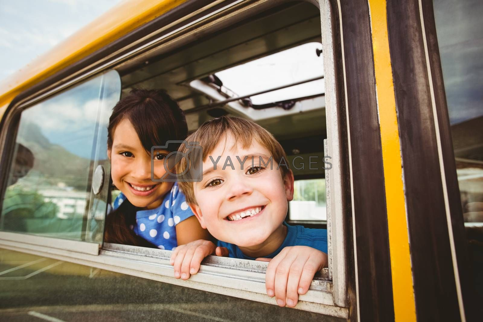 Cute pupils smiling at camera in the school bus by Wavebreakmedia