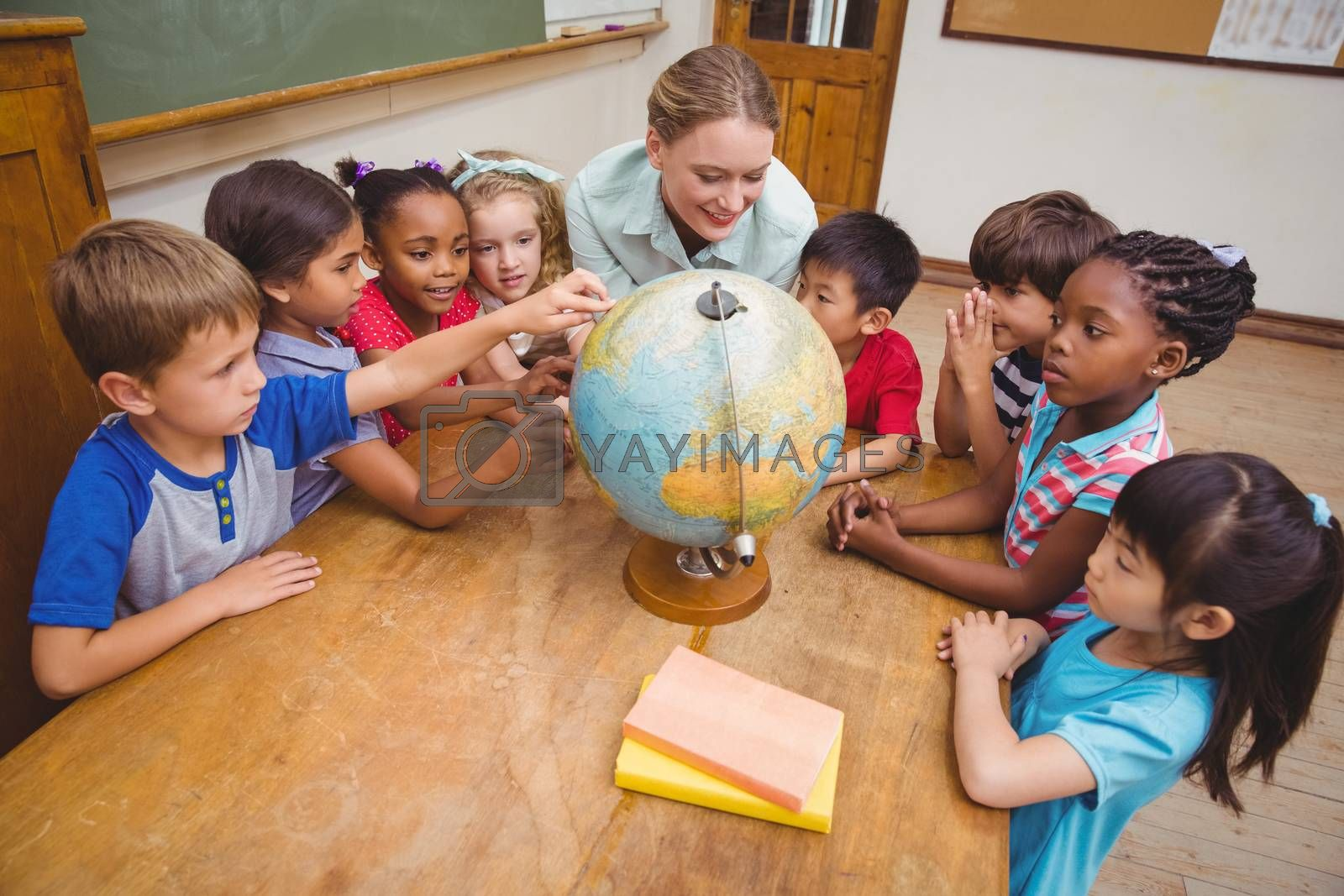 Cute pupils and teacher in classroom with globe at the elementary school