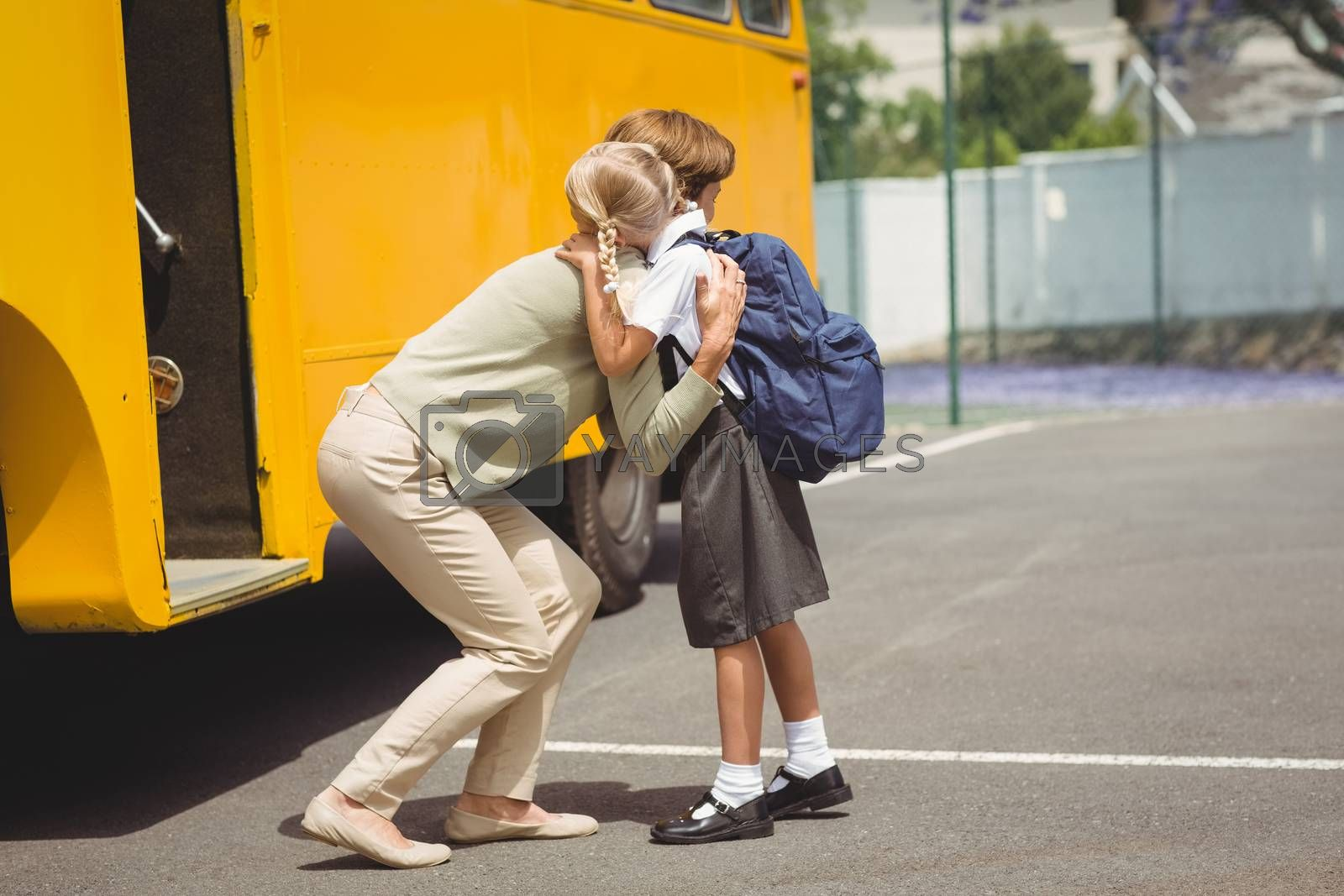 Mother hugging her daughter by school bus outside the elementary school