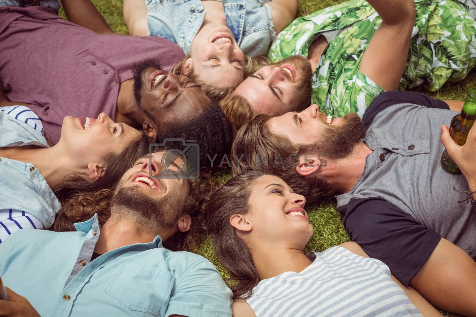 Happy young friends lying on grass on a summers day