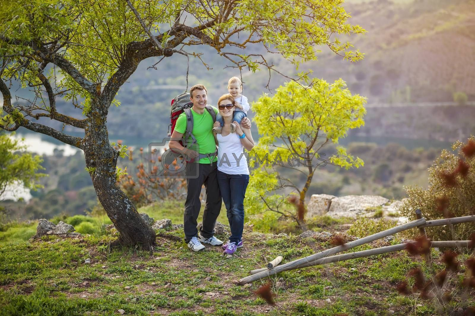 Young couple with toddler boy standing on cliff and enjoying valley view