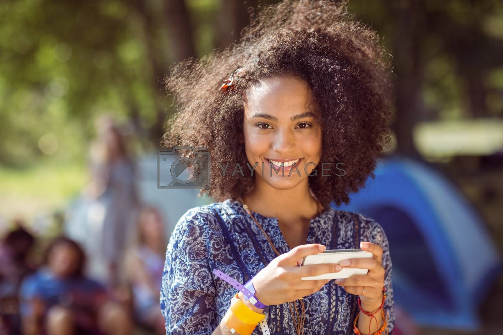 Pretty hipster sending text message at a music festival