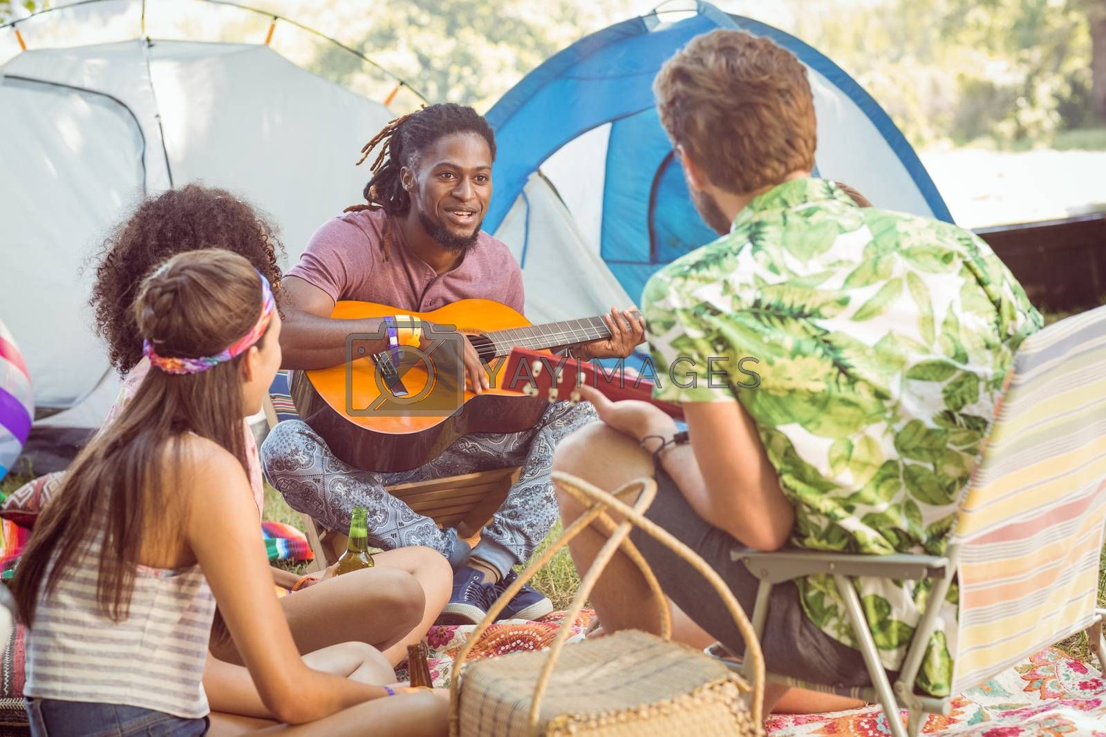 Hipster playing guitar for his friends  at a music festival
