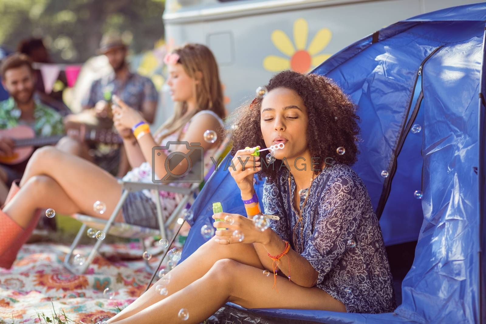 Carefree hipster blowing bubbles in tent at a music festival