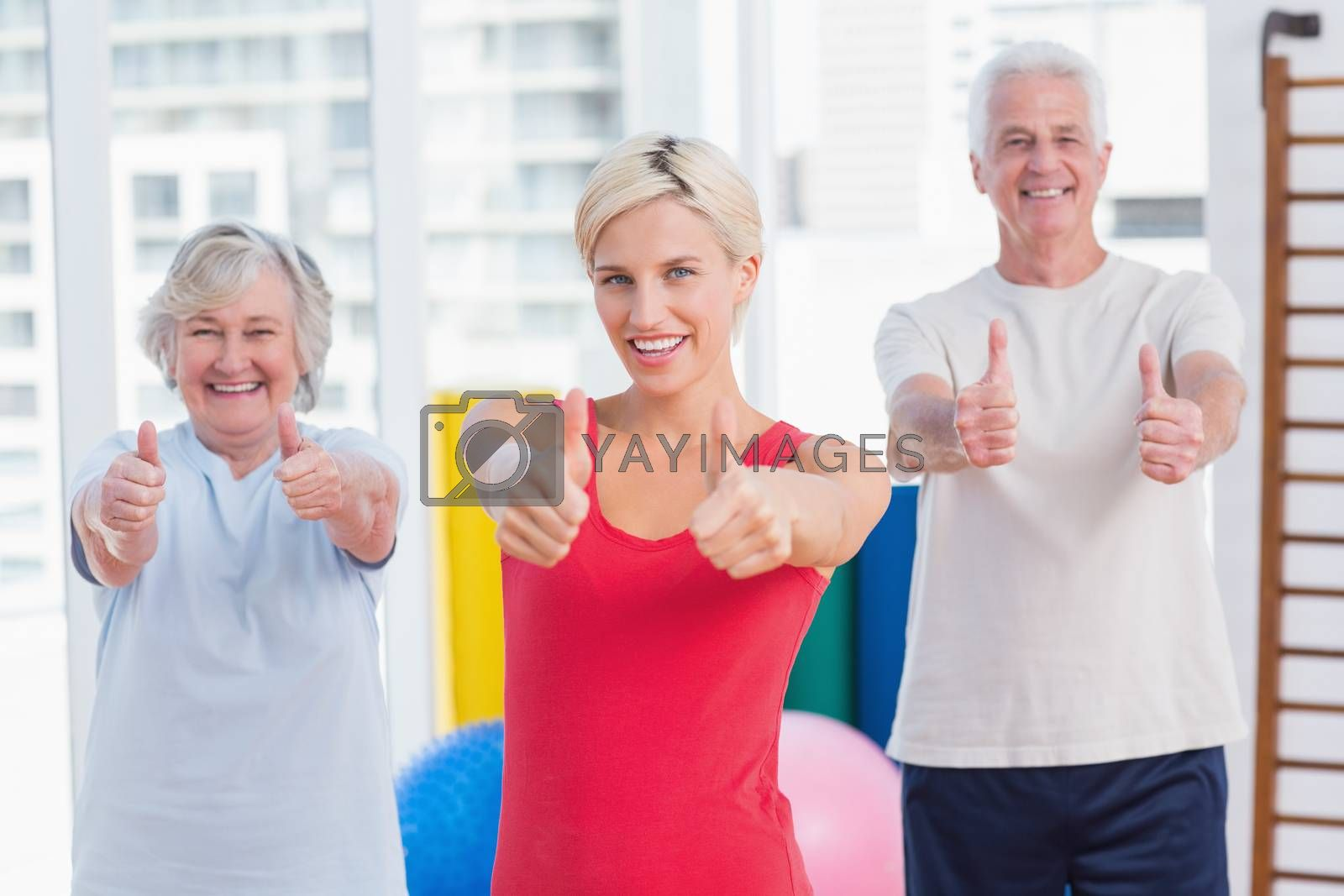 Portrait of confident female instructor with senior couple showing thumbs up in gym