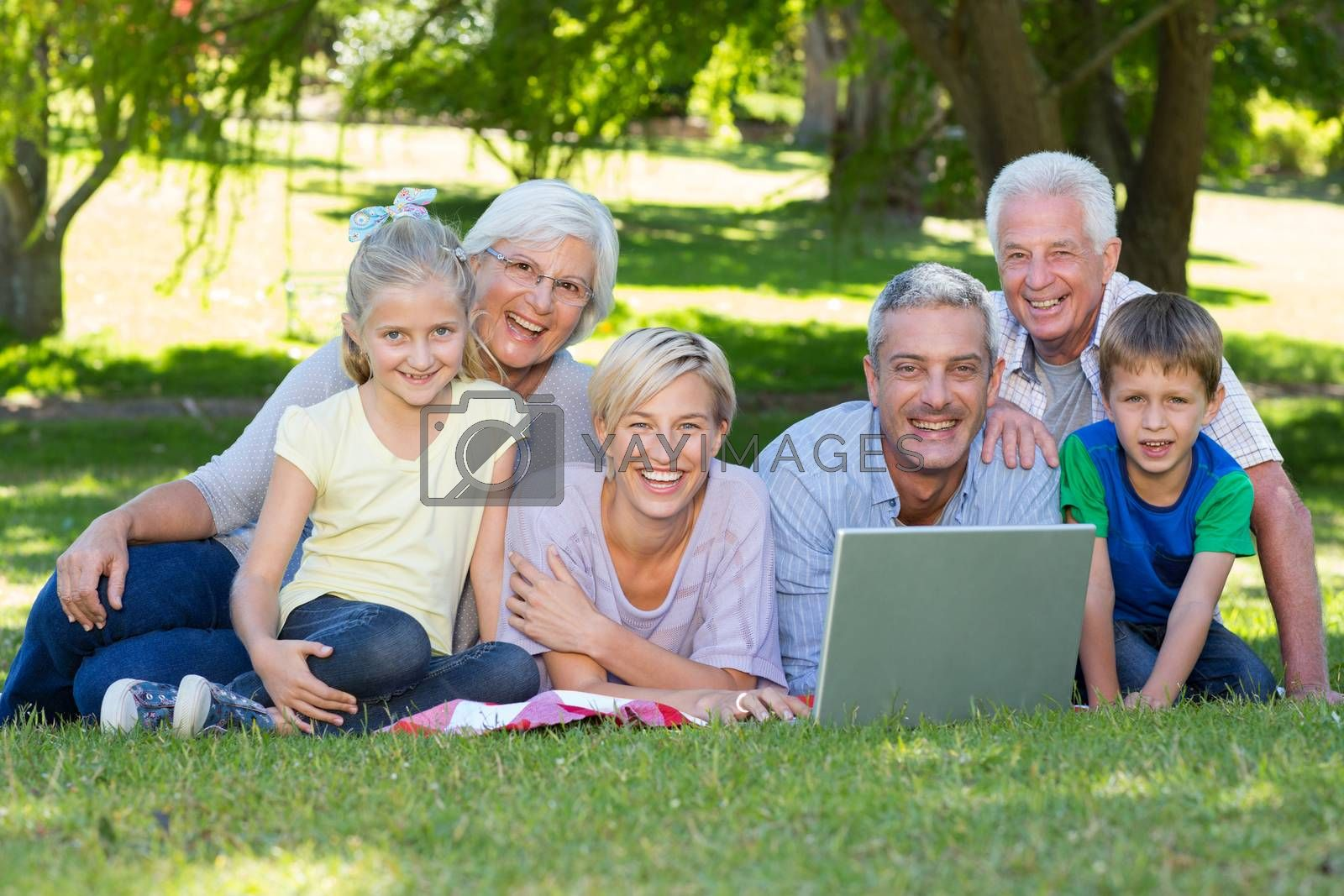 Happy family using laptop in the park on a sunny day