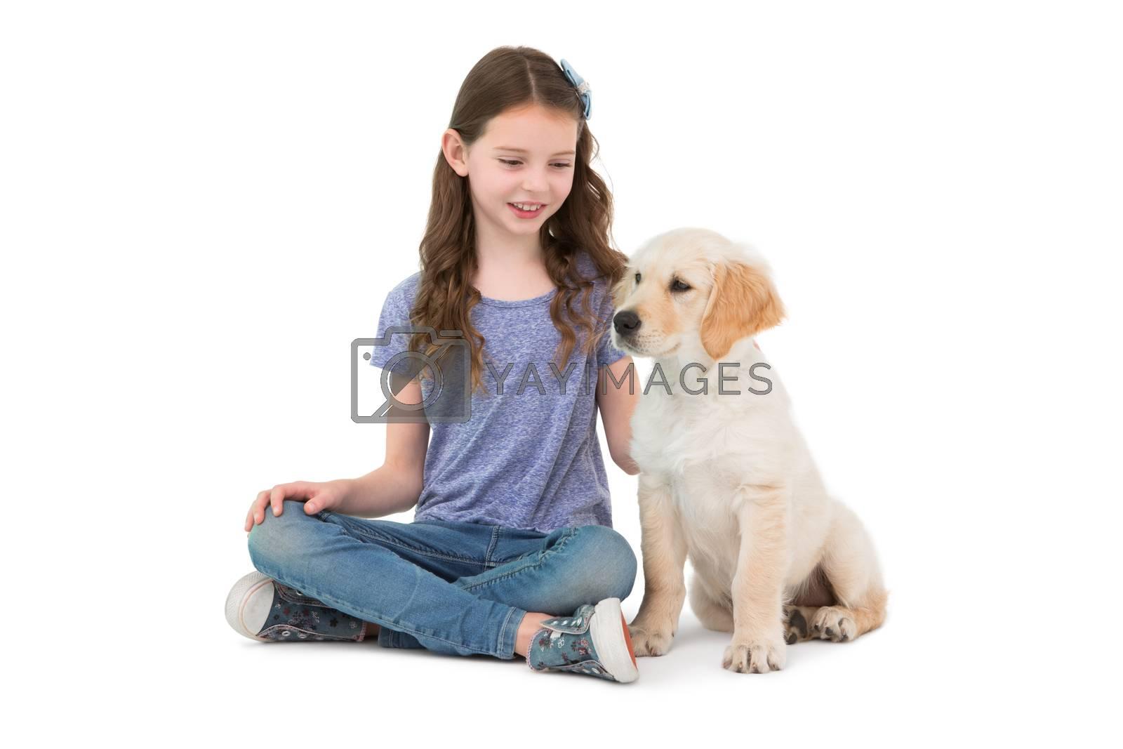 Smiling little girls sitting next to dog on white background
