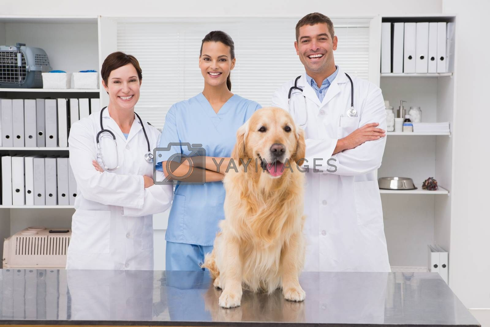 Veterinarian coworker smiling at camera with dog  in medical office