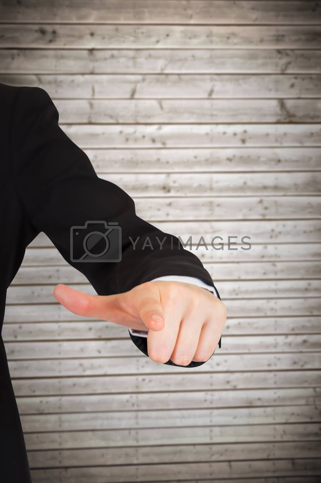 Businesswoman pointing against wooden planks background