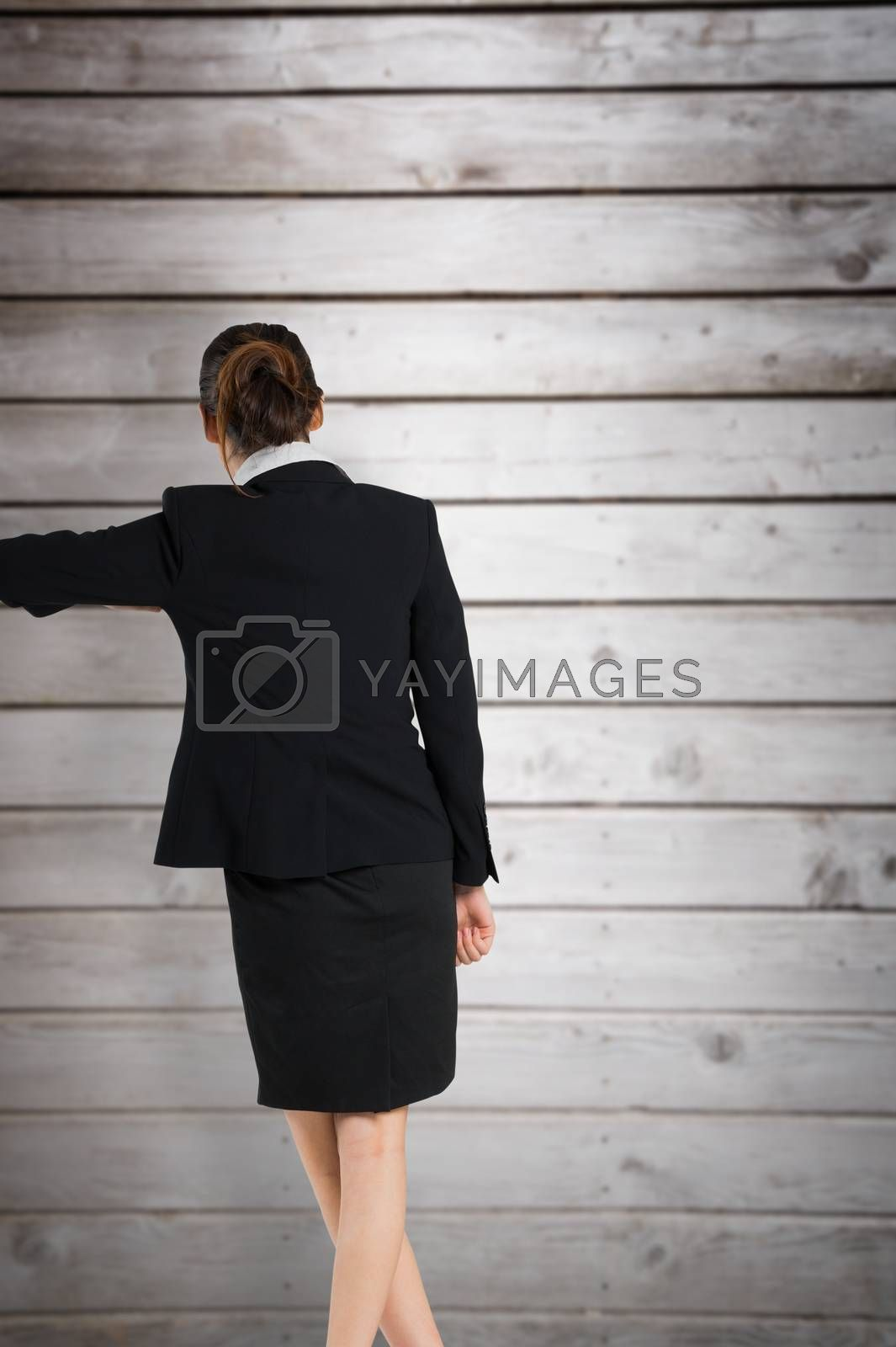 Young businesswoman standing and leaning against wooden planks