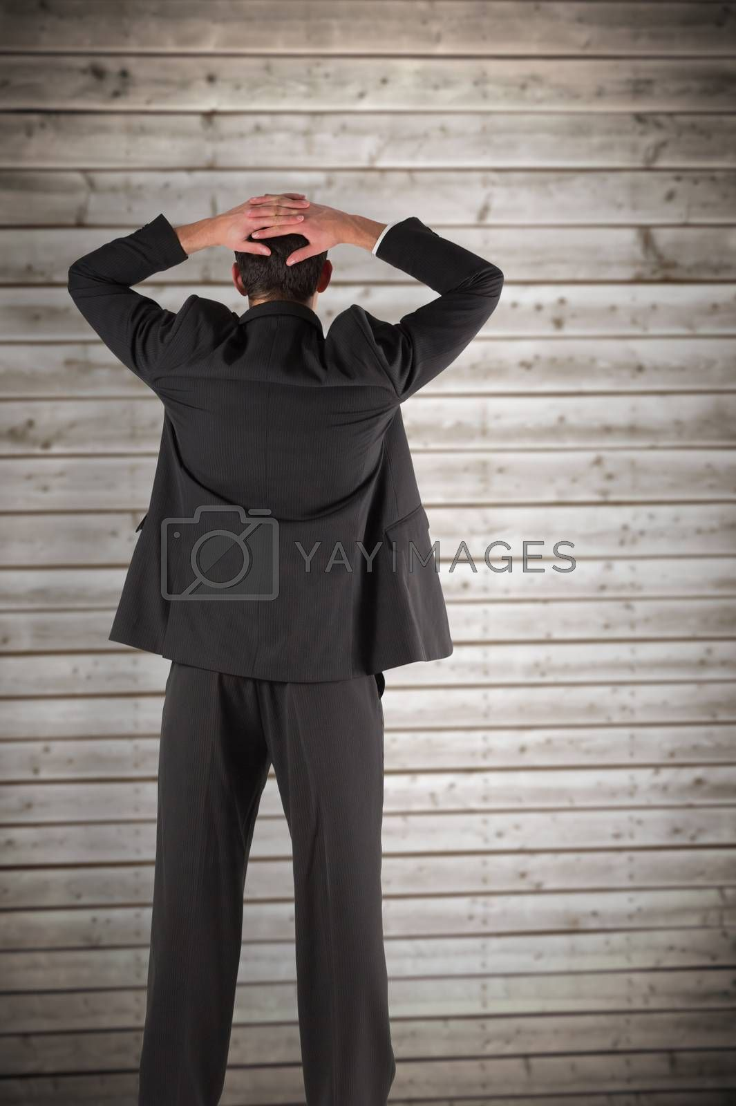 Businessman standing back to the camera with hands on head against wooden planks background