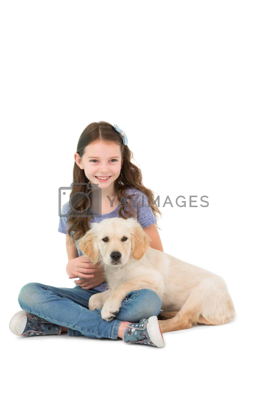Happy little girl sitting with dog on her legs on white background