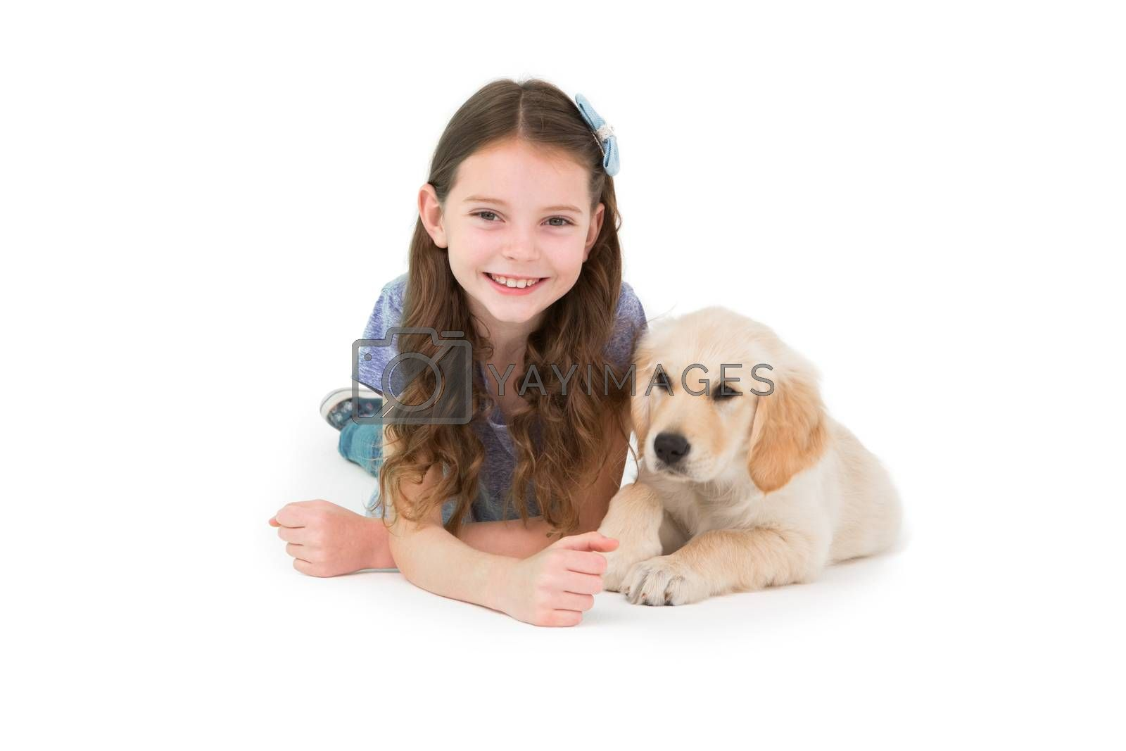 Lying little girl with a dog on white background