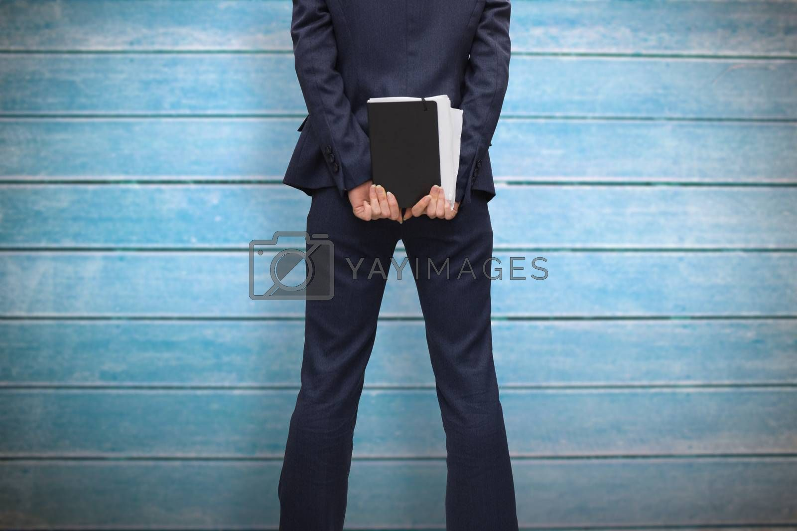 Businesswoman holding diary against wooden planks