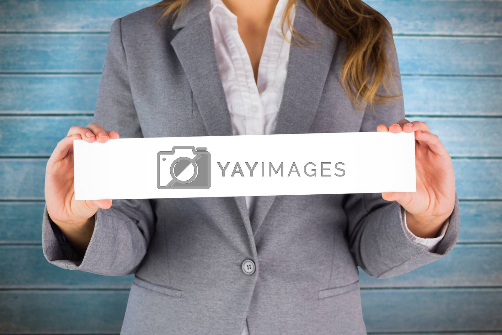 Businesswoman showing a card against wooden planks